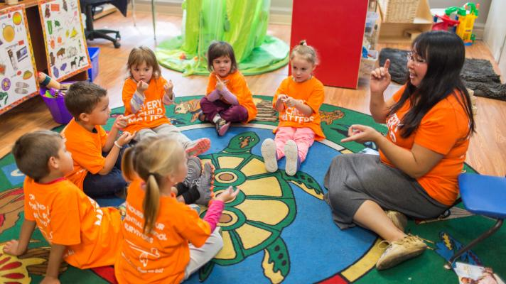 Image of early childhood educator in story circle with children